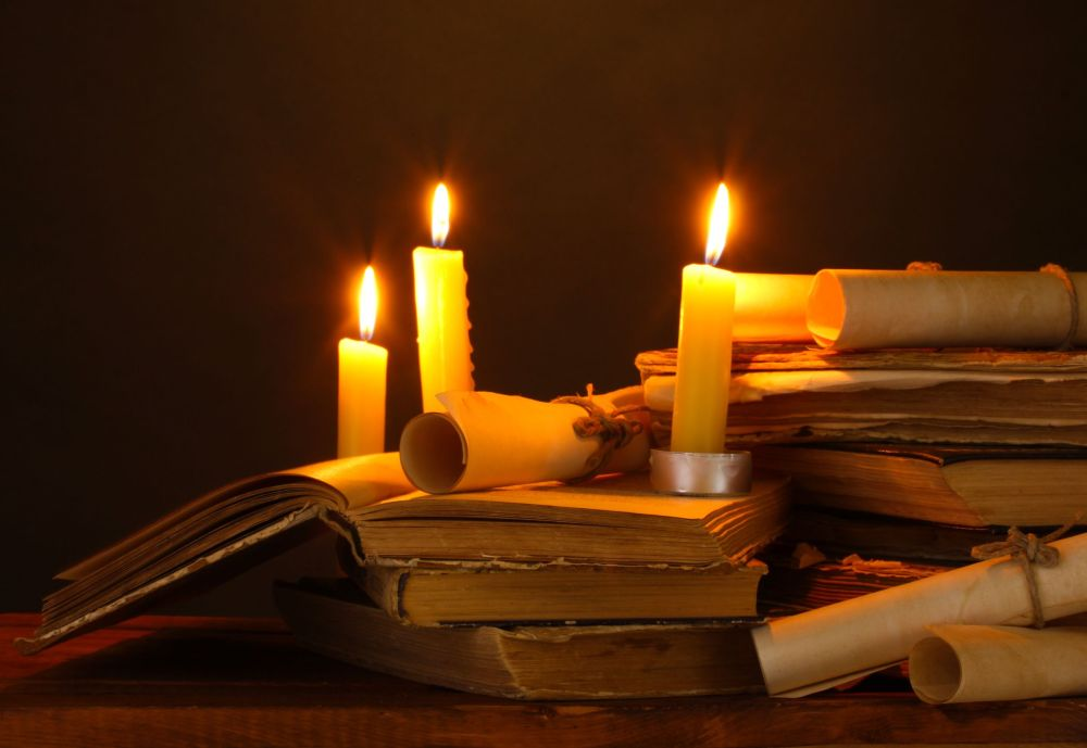 19510605 - pile of old books with candle and scroll in dark